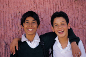 Two young boys, smiling with an arm around each other.